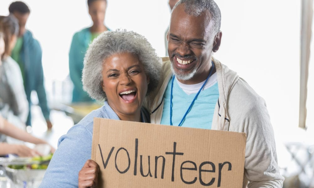 "happy couple holding a ""volunteer"" sign at food bank"