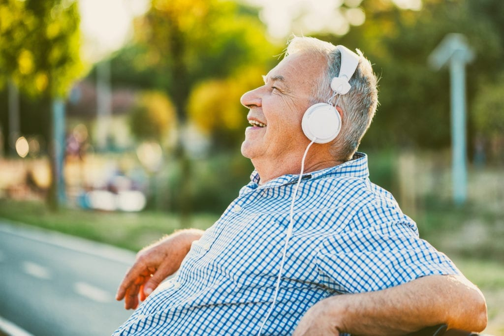 Outdoor photo of senior man who is listening music on headphones.