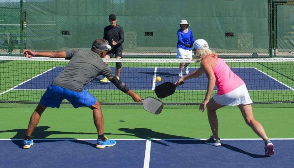 senior couples playing doubles pickleball game