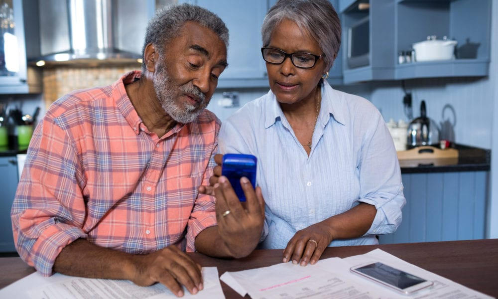 Couple using calculator while discussing finances in kitchen