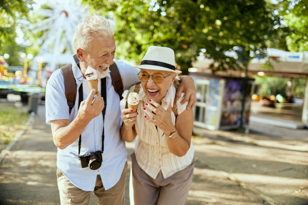 senior couple eating ice cream at amusement park
