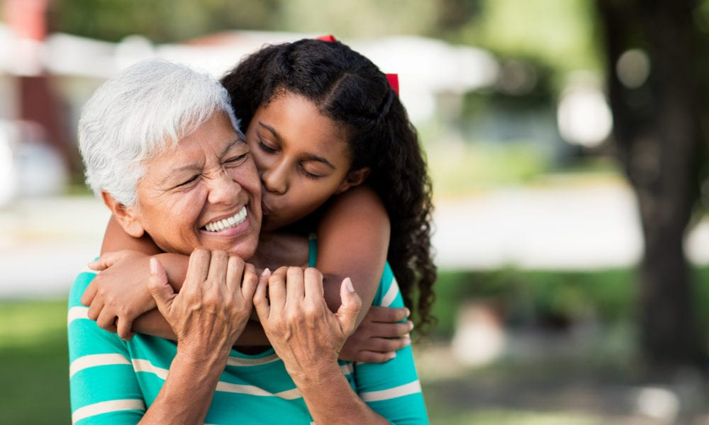 A loving teen girl embracing and kissing her happy grandmother from behind and holding each other outdoors.