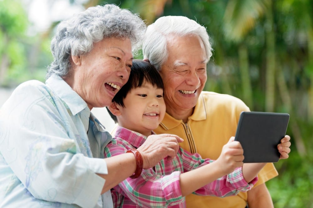 seniors using tablet computer with grandchild in the middle