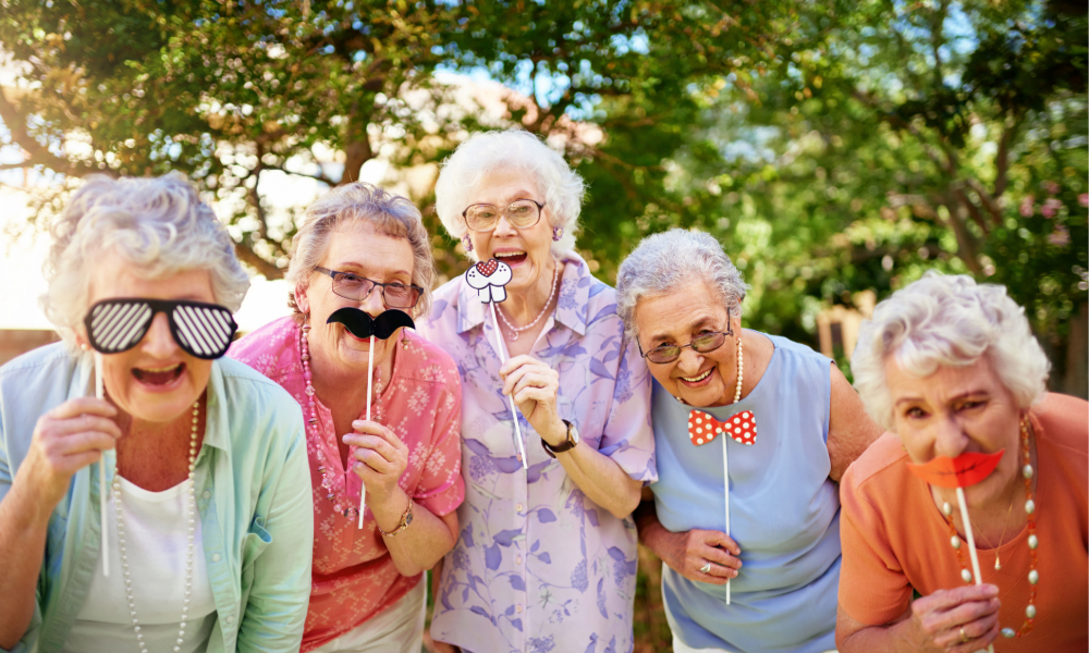 senior women at retirement community holding photo booth props